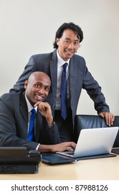 Portrait of smiling business people working on laptop