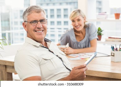 Portrait of a smiling business team holding a tablet at the office