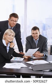 Portrait of smiling business team holding document in office.