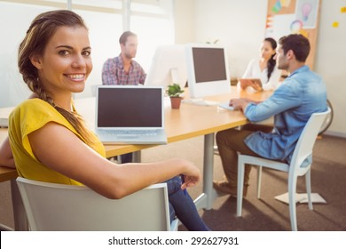 Portrait of smiling business team working on laptops in a bright office