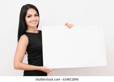 Portrait of smiling business woman with blank white sign board. Isolated studio portrait.