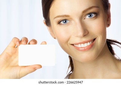 Portrait of smiling business woman giving blank business card, at office