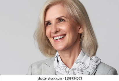 Portrait of smiling business woman looking away. Middle aged lady isolated on grey