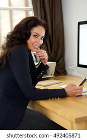 Portrait of a smiling business woman with mobile phone in the office