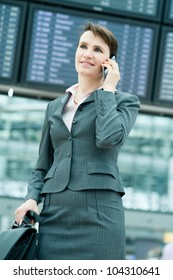 Portrait of smiling business woman on mobile phone in front of panel at airport