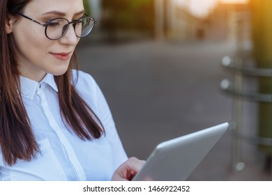 Portrait of smiling business woman using tablet pc in front of office building.