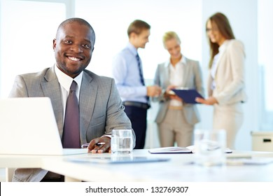 Portrait of a smiling businessman being at his workplace