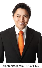 Portrait of a smiling businessman in a black suit and orange tie standing against a white background.