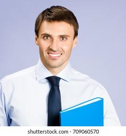 Portrait of smiling businessman with blue folder, against violet background