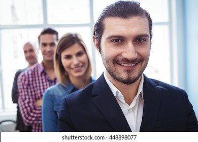 Portrait of smiling businessman with colleagues standing in row at creative office - Shutterstock ID 448898077