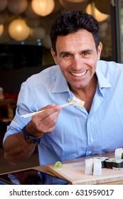 Portrait of smiling businessman eating sushi with chopsticks