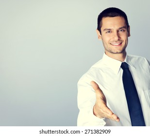 Portrait of smiling businessman giving hand for handshake, with blank copyspace area for text or slogan, specially toned