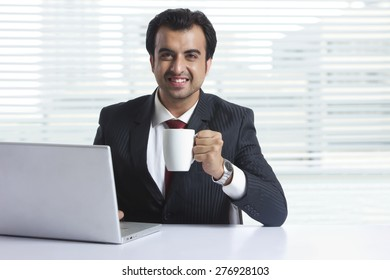 Portrait of smiling businessman having coffee while working in office