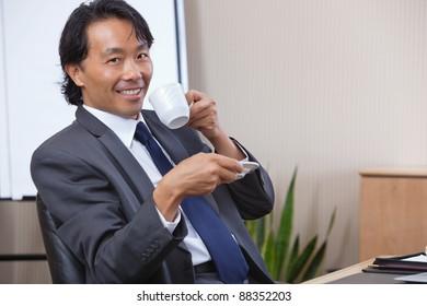 Portrait of smiling businessman having coffee