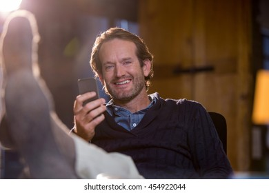 Portrait of smiling businessman holding cellphone while relaxing in creative office