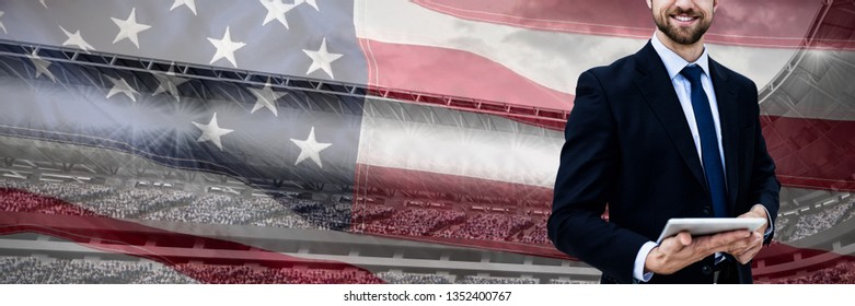 Portrait of smiling businessman holding digital tablet against close-up of an american flag
