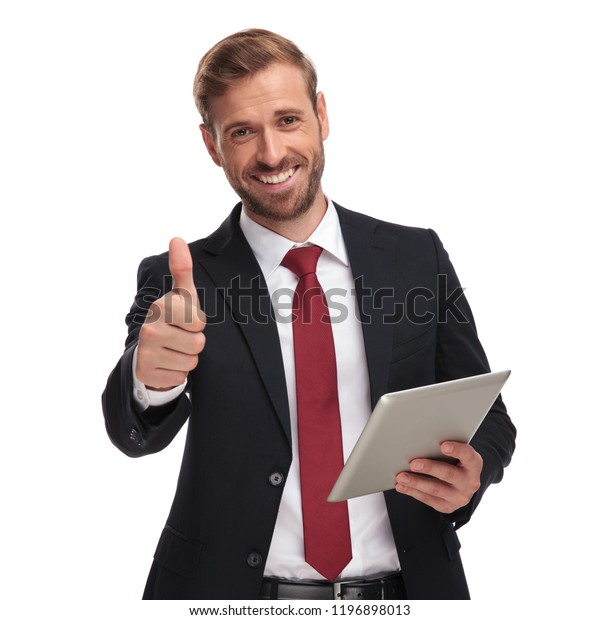 portrait of smiling businessman holding tablet and making ok sign while standing on white background