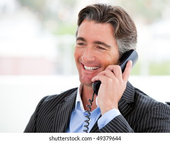 Portrait of a smiling businessman on phone in his office