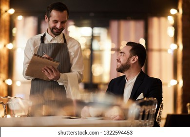 Portrait of smiling businessman ordering food in luxury restaurant with waiter standing at table, copy space