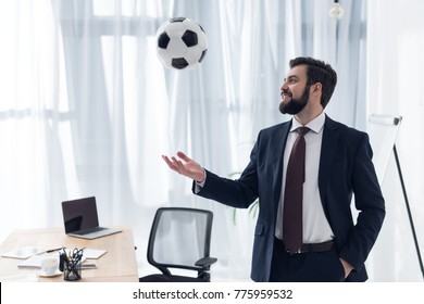 portrait of smiling businessman playing with soccer ball at workplace in office