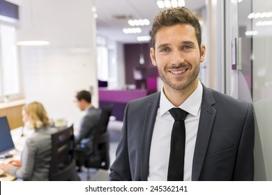 Portrait of smiling Businessman posing  in modern office, looking camera