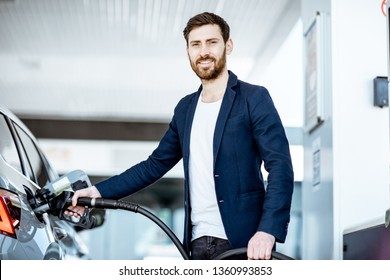 Portrait of a smiling businessman refueling his luxury car at the gas station