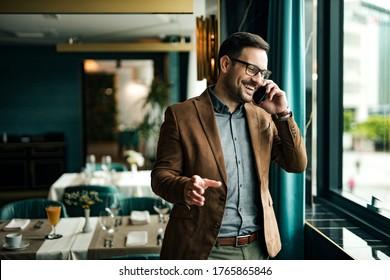 Portrait of a smiling businessman in restaurant talking on smart phone.