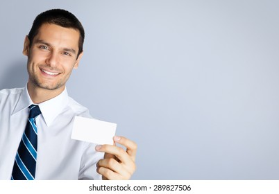 Portrait of smiling businessman showing blank business or plastic credit card, against grey background. Copyspace blank area for slogan or text. Business and success concept.