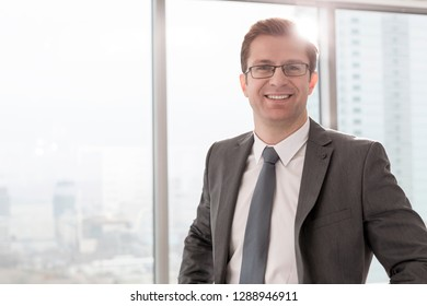 Portrait of smiling businessman standing in boardroom at office
