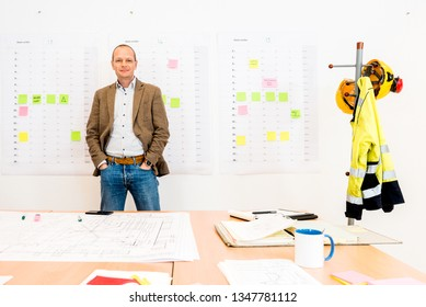Portrait of smiling businessman standing with hands in pockets with blueprint on table at workplace