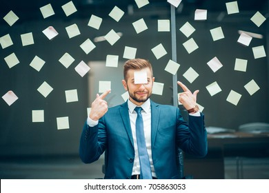 portrait of smiling businessman with sticky notes on face sitting against glass wall