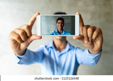 Portrait of smiling businessman taking selfie with smartphone. Young Indian student standing at wall posing for photo. Social networking concept