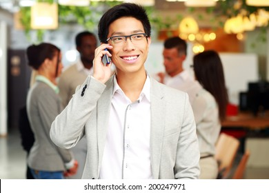 Portrait of a smiling businessman talking on the smartphone in front of colleagues