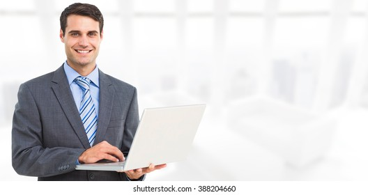 Portrait of smiling businessman using laptop against modern room overlooking city