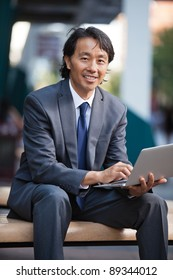 Portrait of smiling businessman using laptop outdoors