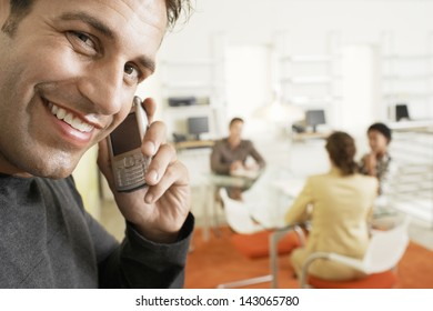 Portrait of smiling businessman using mobile phone with colleagues discussing in background
