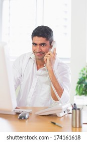 Portrait of smiling businessman using phone and computer at desk in office