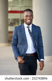 Portrait of a smiling businessman walking in the city