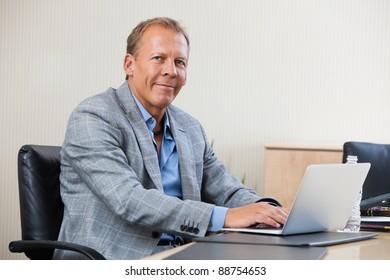 Portrait of smiling businessman working on laptop