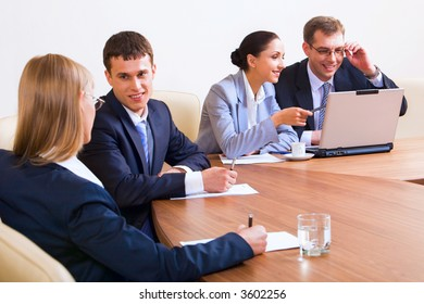 Portrait of smiling businesspeople discussing different questions sitting around the table with an opened laptop, documents and glasses of water