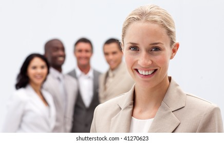 Portrait of smiling businesswoman in front of her multi-ethnic team