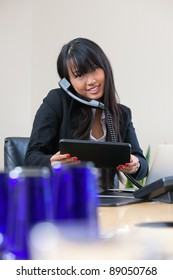 Portrait of smiling businesswoman having conversation on phone with digital tablet in hand