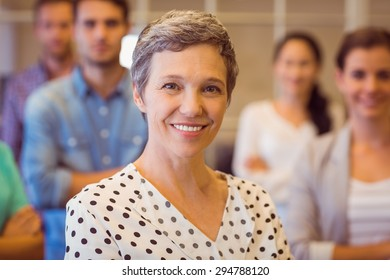 Portrait of a smiling businesswoman with her team in the background