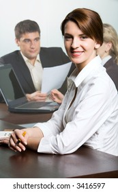 Portrait of smiling businesswoman looking at camera holding yellow pen and two businesspeople working on laptop sitting at the table on the background