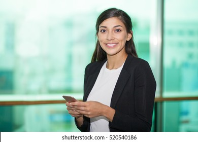 Portrait of smiling businesswoman with mobile phone