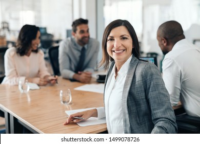 Portrait of a smiling businesswoman sitting with a group of diverse colleagues around a boardroom table during an office meeting