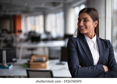 Portrait of smiling businesswoman standing in office.