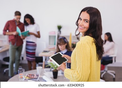 Portrait of smiling businesswoman with tablet computer in office