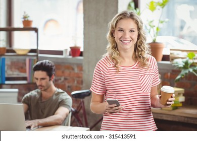 Portrait of smiling businesswoman using smartphone while holding coffee in creative bright office
