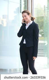 Portrait of a smiling businesswoman walking outside with cell phone